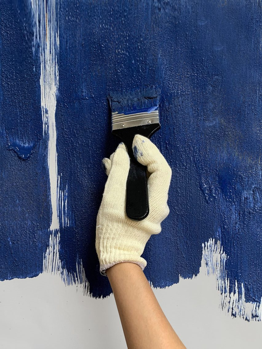 Hand applying blue Celour paint with a brush