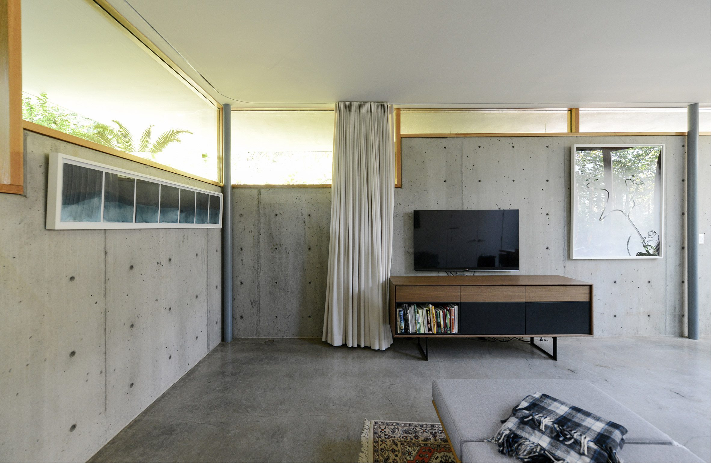 concrete living room with wood framed windows by No Architecture