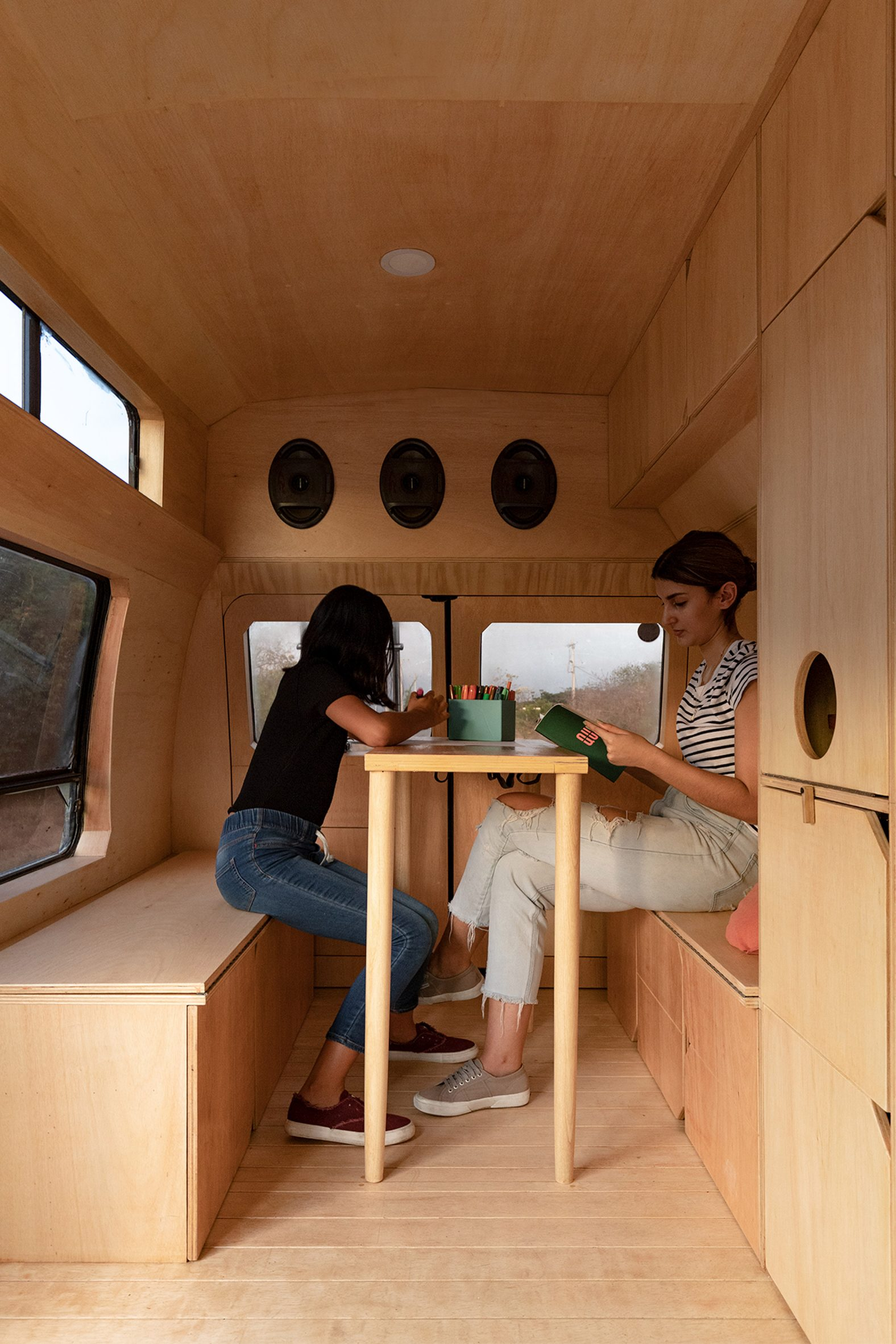 A woman and her daughter sit at a table inside Dodo Van