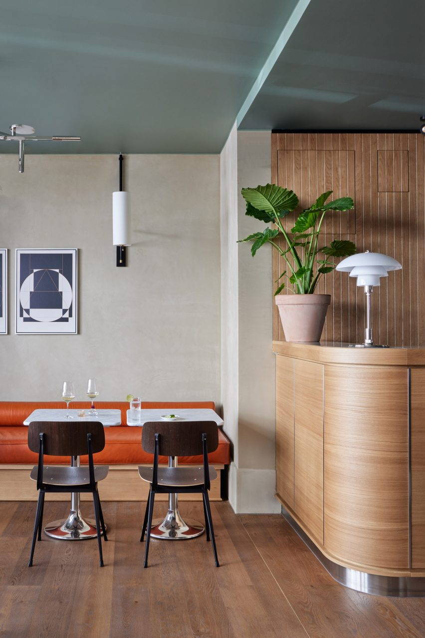 Curved wooden bar and bench seating upholsterd in orange leather in hotel interior by Fettle