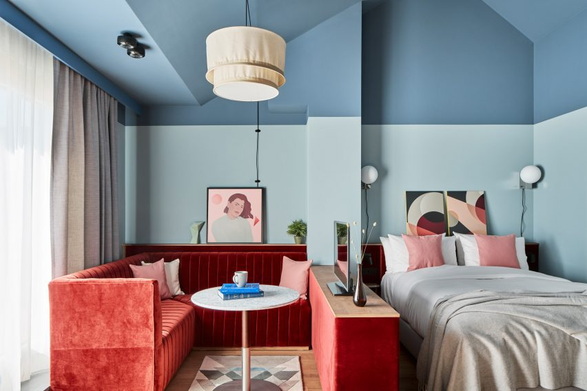 Guest apartment interior by Fettle with two-tone blue walls and red velvet seating nook