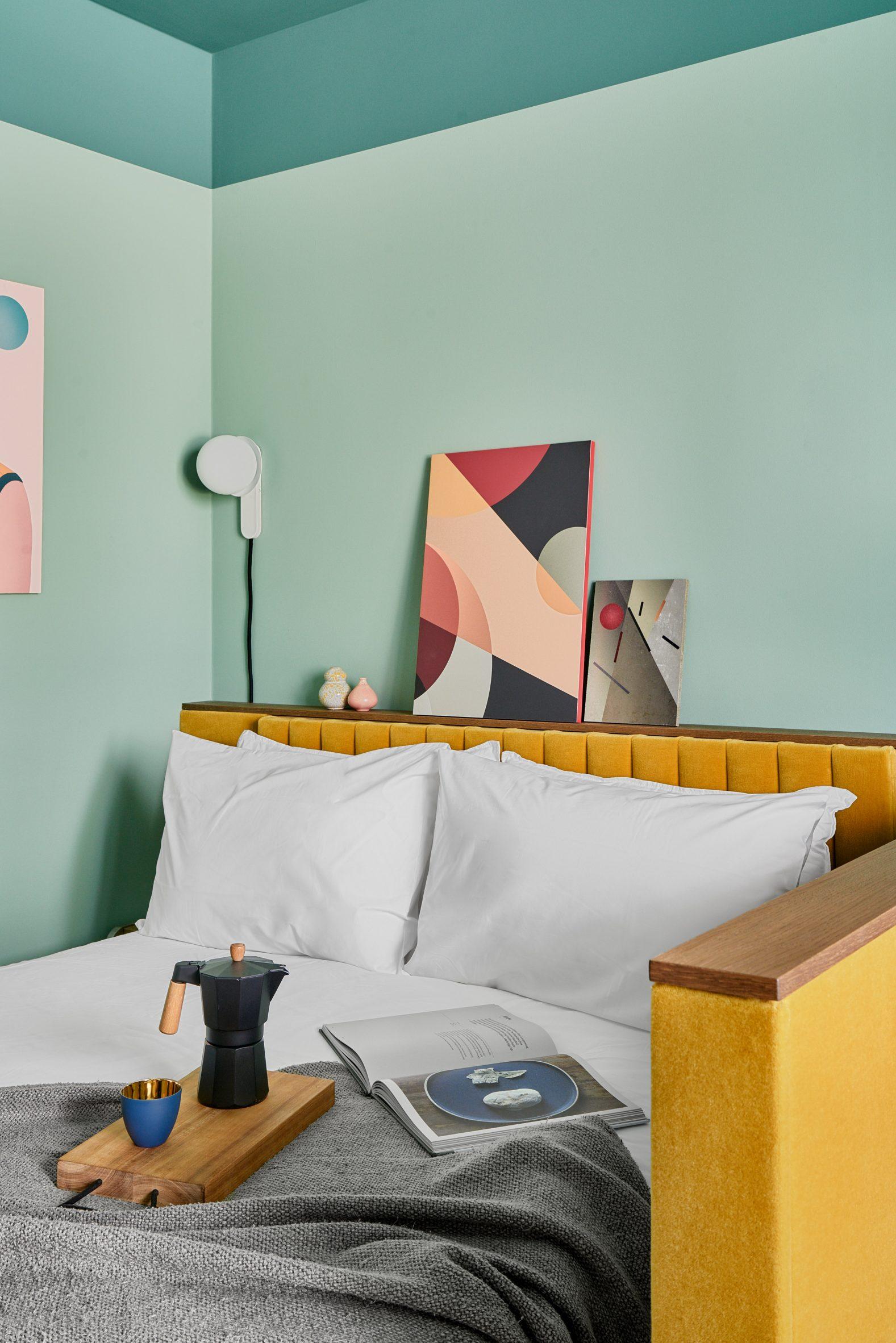 Yellow upholstered bed in guest bedroom of Schwan Locke hotel