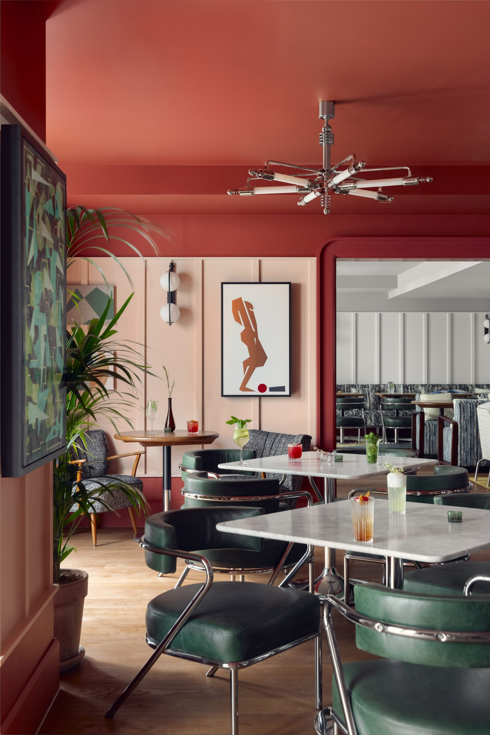 Restaurant of Schwan Locke hotel with red walls, green leather chairs and marble tables