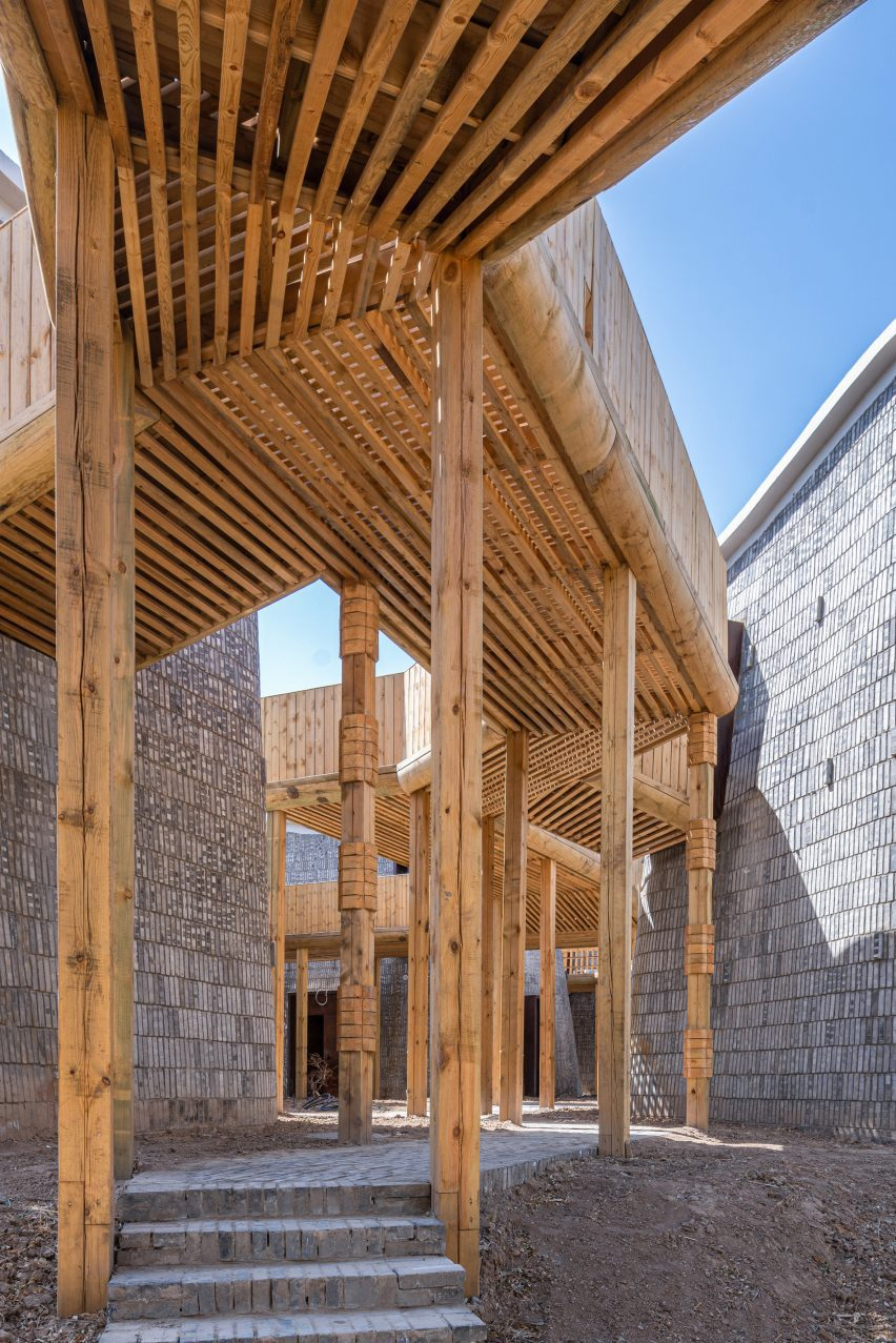 Worm's eye view of wooden walkway connecting buildings designed by Studio AVOID