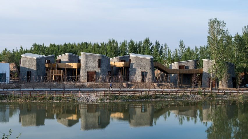 Brick-clad pods connected by wooden walkway in Grotto Retreat Xiyaotou