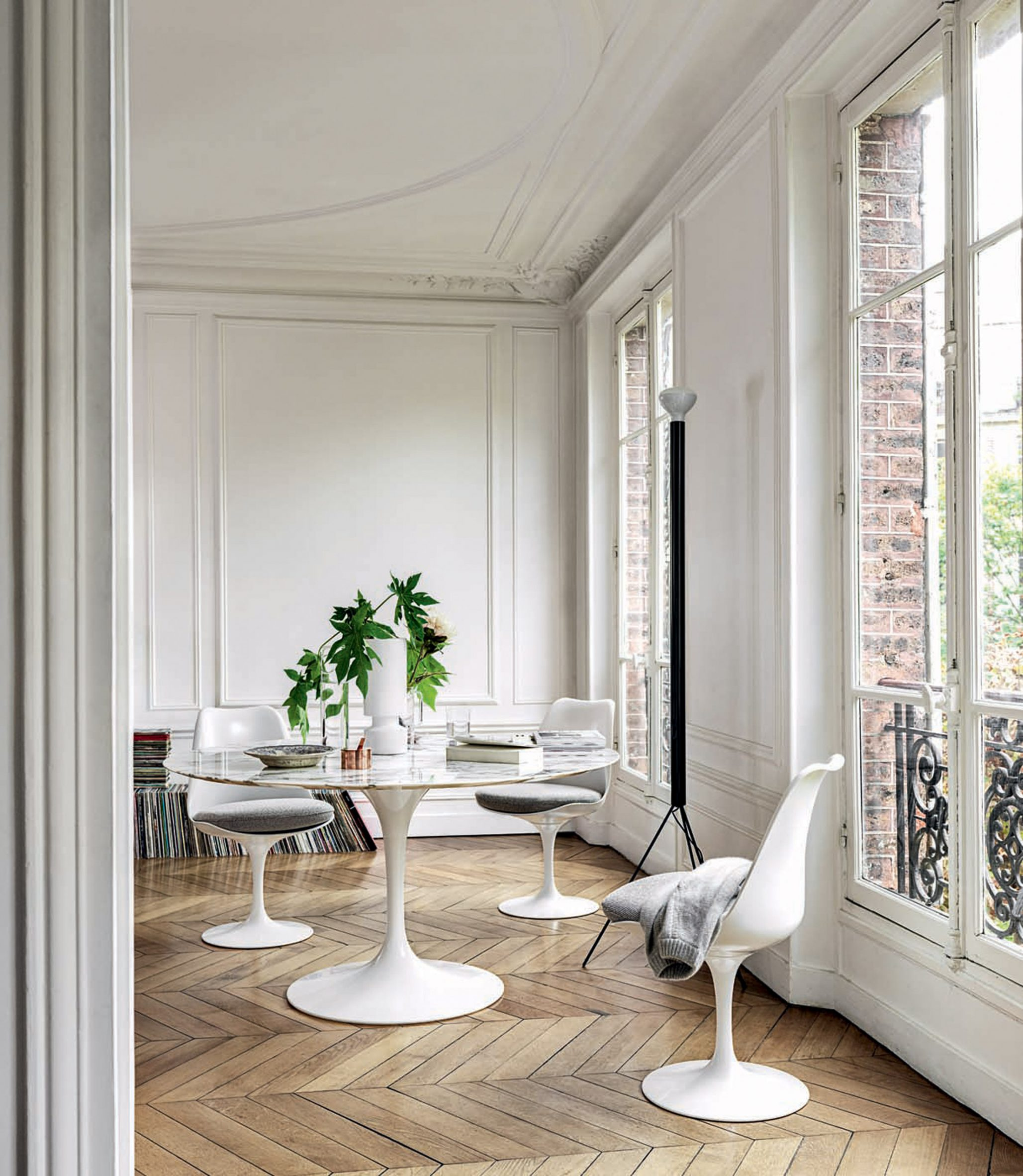 A modern white dining table set in white plastic with pedestal bases in a classic home interior