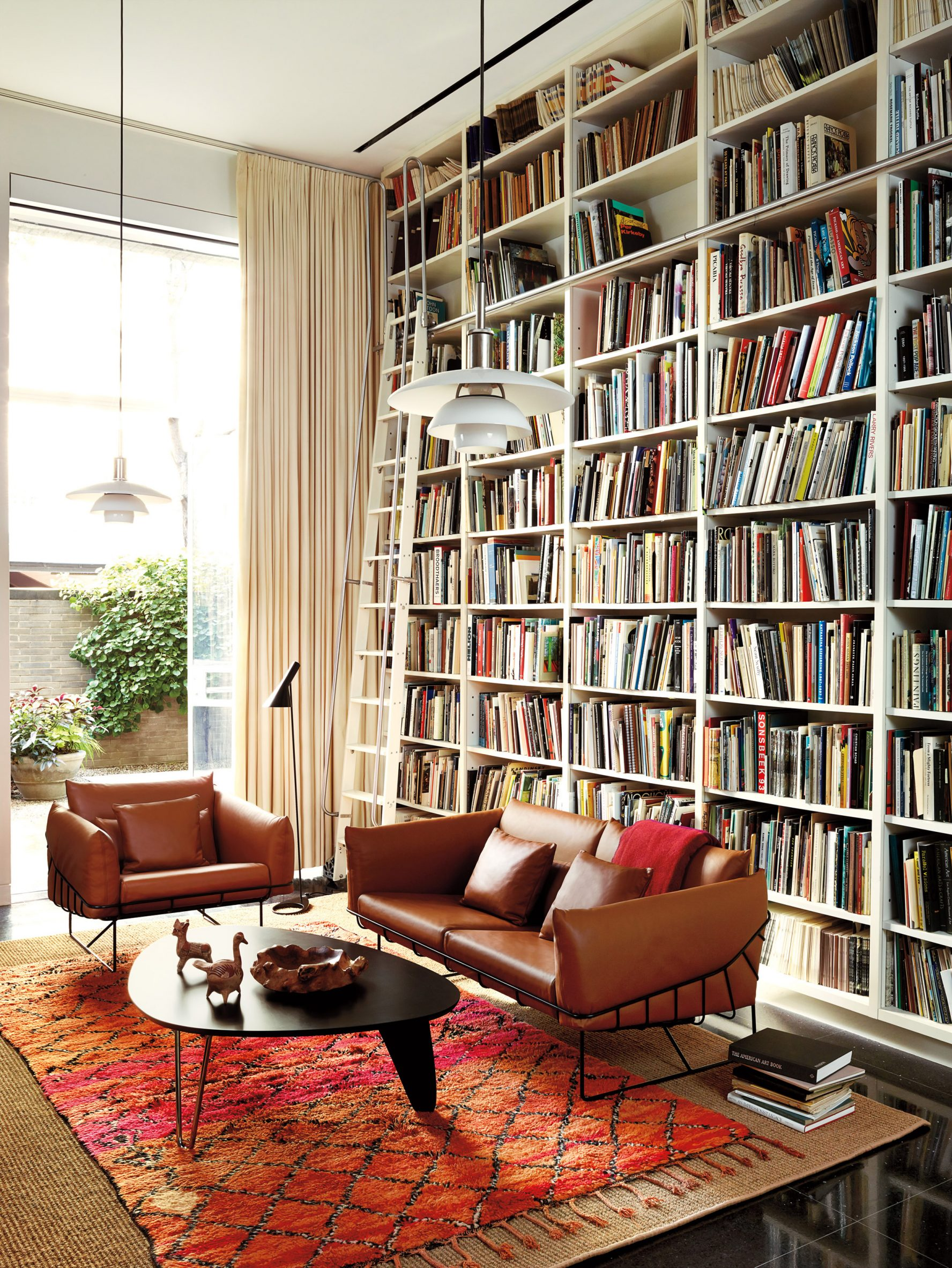 Brown leather sofas with a black wire frame next to a coffee table with an egg shaped top in a book-lined living room