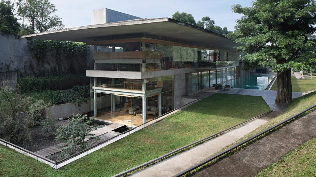 Giant concrete roof shelters home in Indonesia by Adramatin