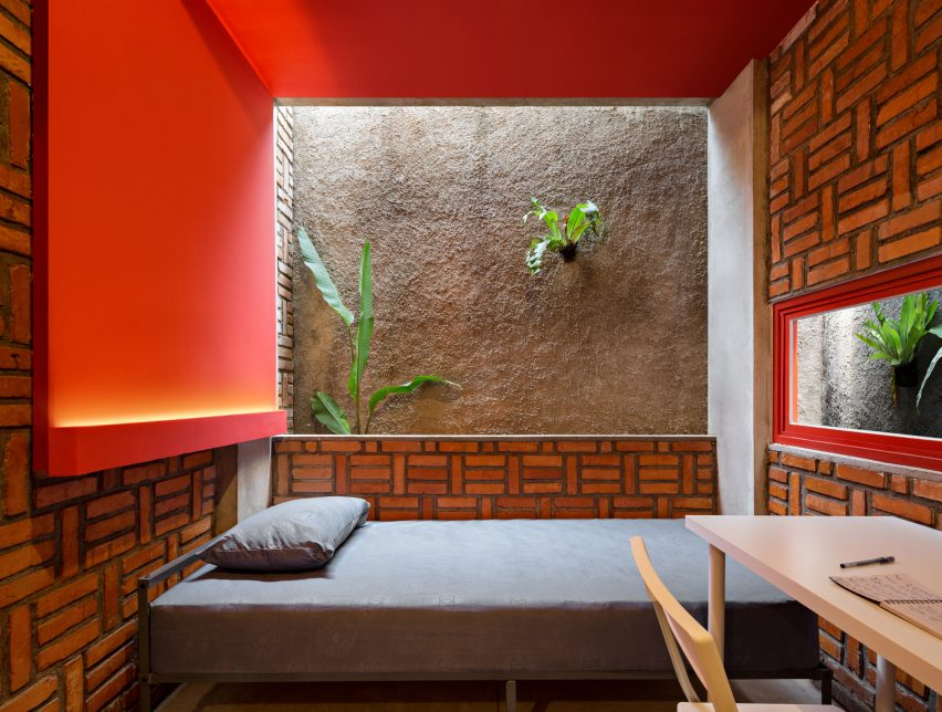 Dormitory room with walls showing a contrast of red paint, brickwork, concrete and greenery