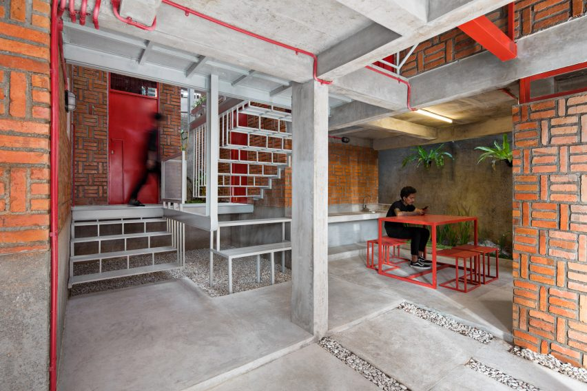 Resident sits at red table under a white metal staircase