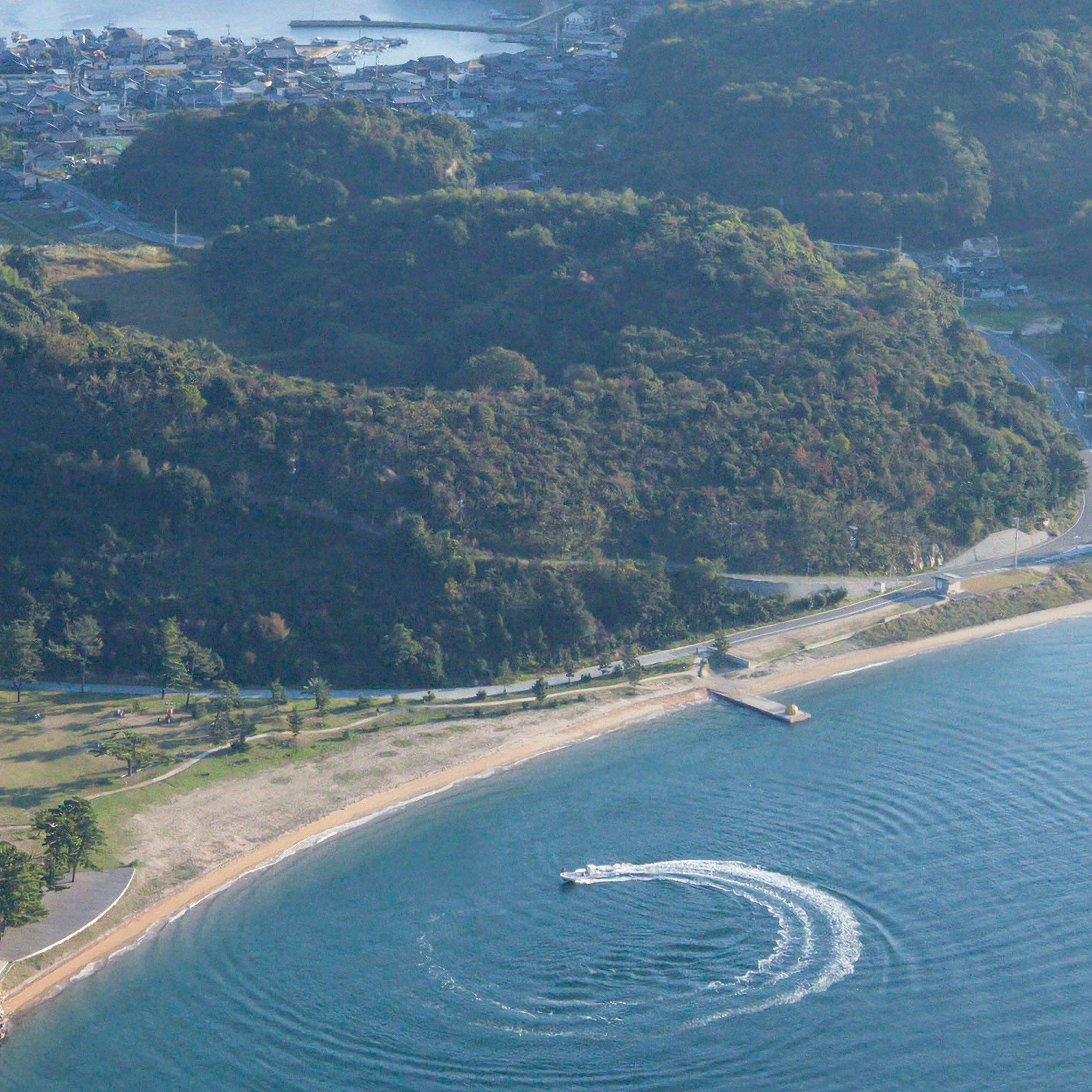 An aerial photo of Naoshima Island showing Kusama's pumpkin sculpture on a pier