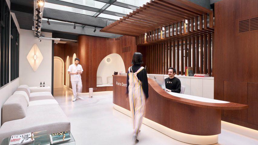 A patient walks to the wooden reception desk in Paris Dental Studios