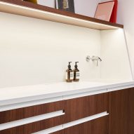 A white sink with wooden cupboards