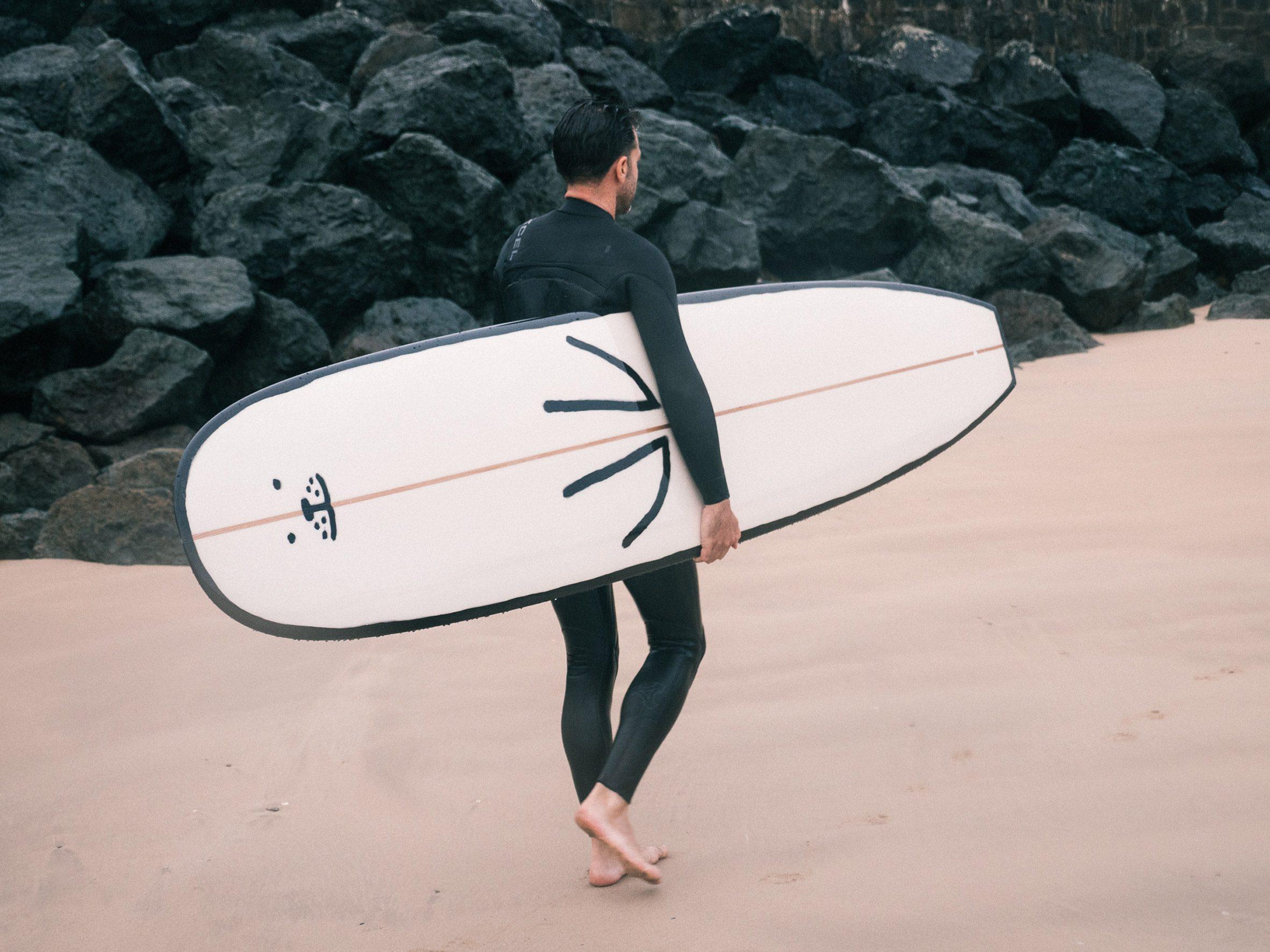 A surfer carries the seal surfboard across a beach