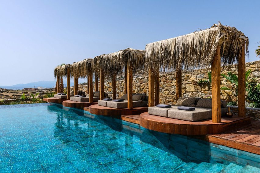 Sunbeds on round wooden platforms next to pool with turquoise tiles in hotel by Kyriakos Tsolakis Architects