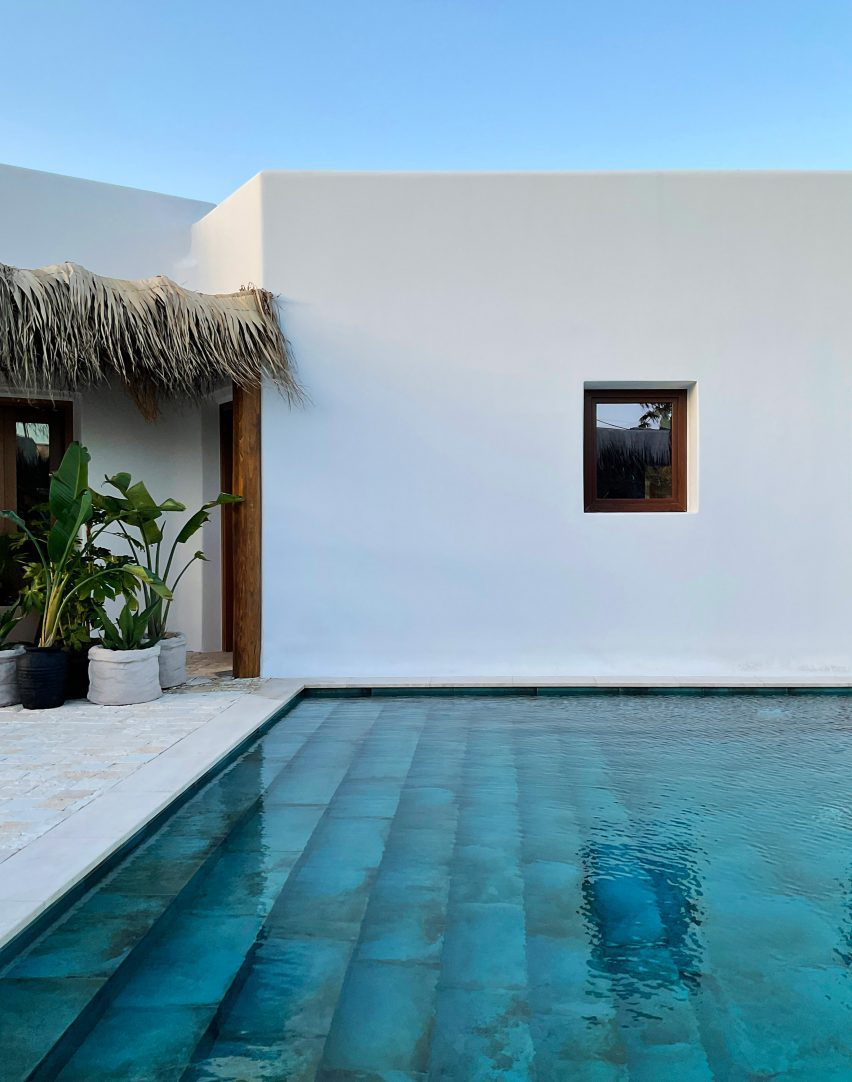 Pool with turqoise tiles in front of whitewashed building by Kyriakos Tsolakis Architects