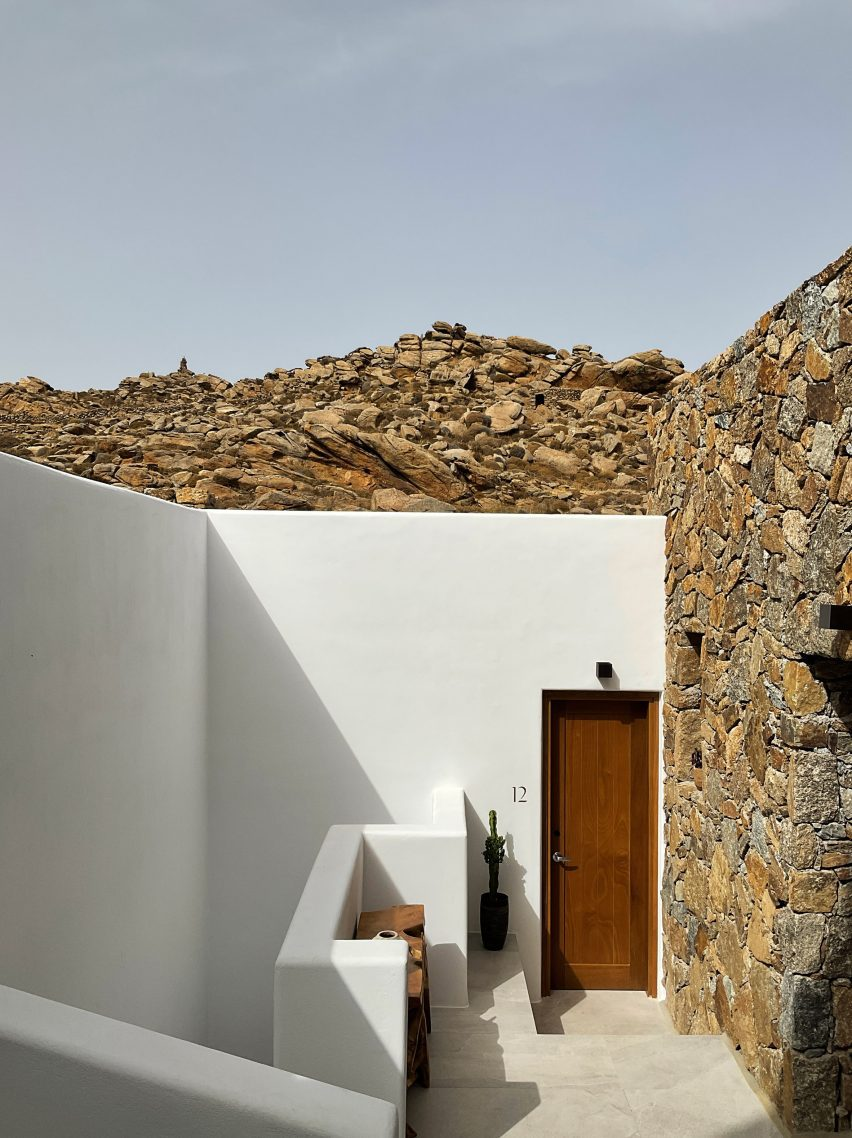 Entrance to Mykonos Wellness Resort with one whitewashed wall and one stone one that blends into the hill
