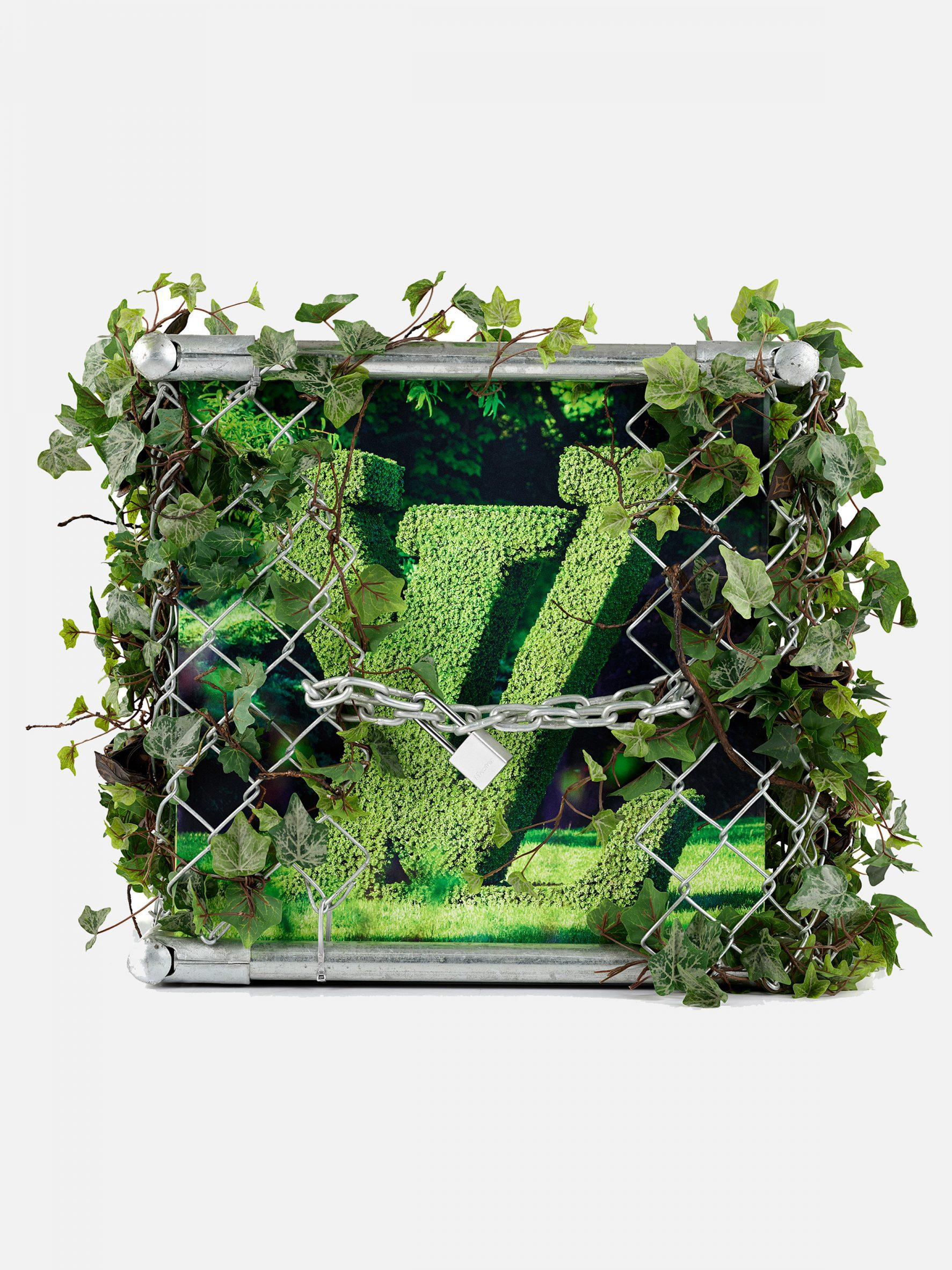 A green Louis Vuitton trunk covered in plants and a silver chain