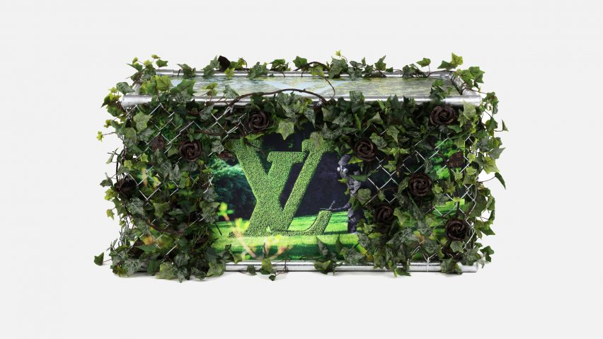 A Louis Vuitton trunk covered in green plants