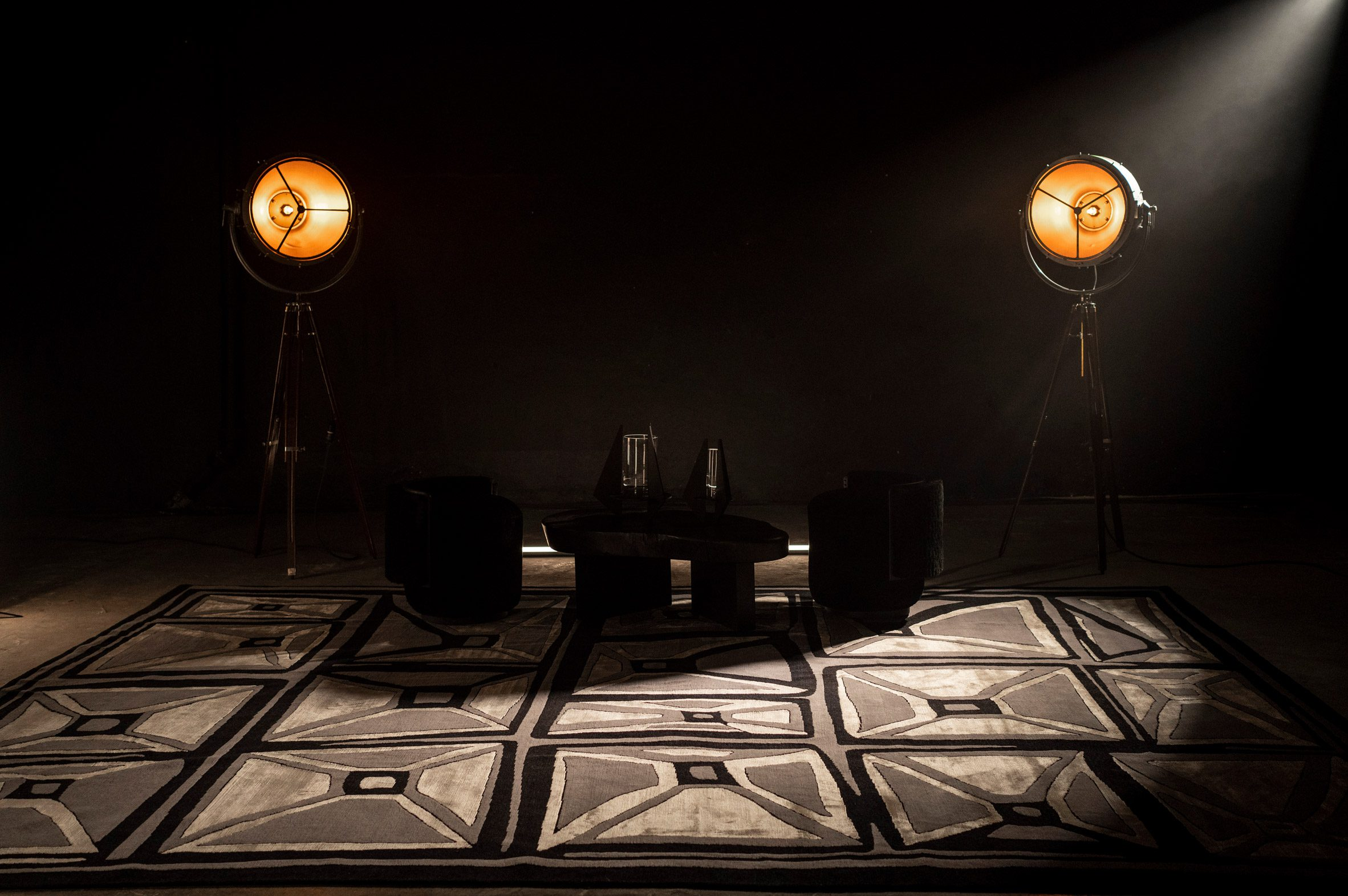 Tables, chairs and lights on a monochrome Meteorito rug