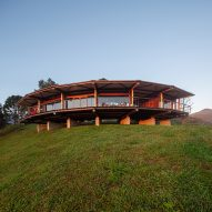 Gui Paoliello Arquiteto completes curved wooden house in Brazil's Morro Cavado valley