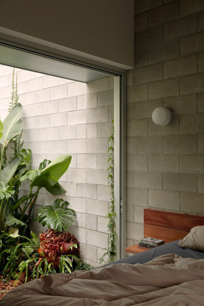 Wooden bed next to floor to large window in Mt Coot-Tha House looking out at plants