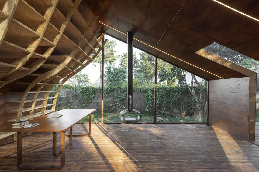 Interior of Writers Cabin with wooden floors curving bookshelf and wood burning stove