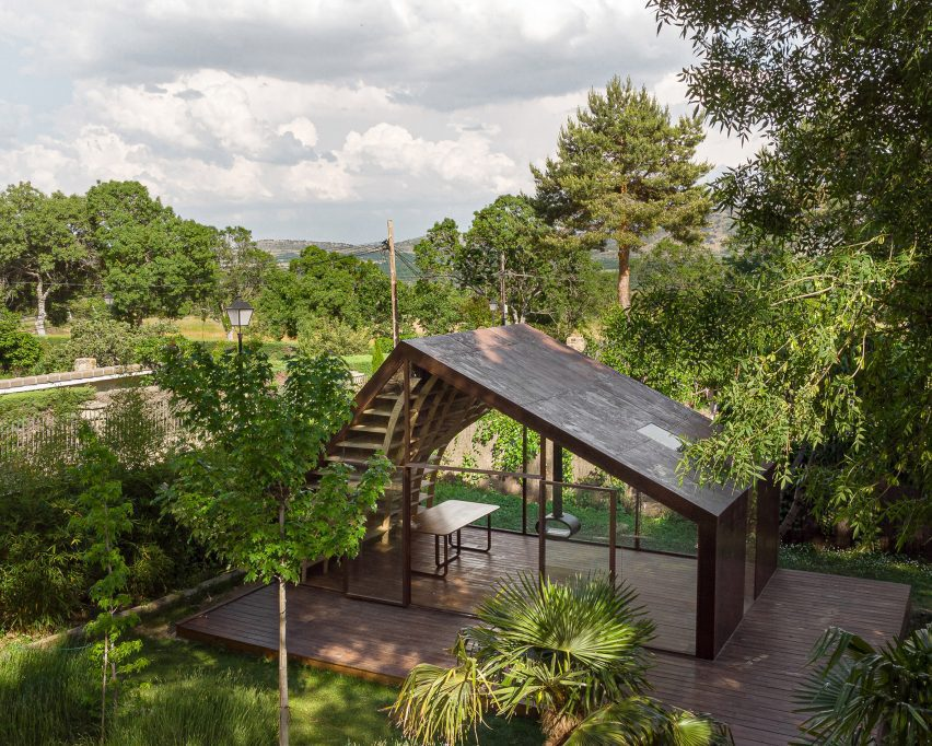 Gabled iron writers cabin on wooden platform in garden