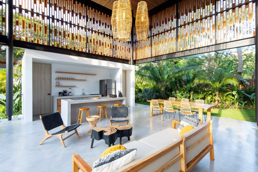 Salón y cocina sin paredes pero con mamparas de madera de Studio Saxe