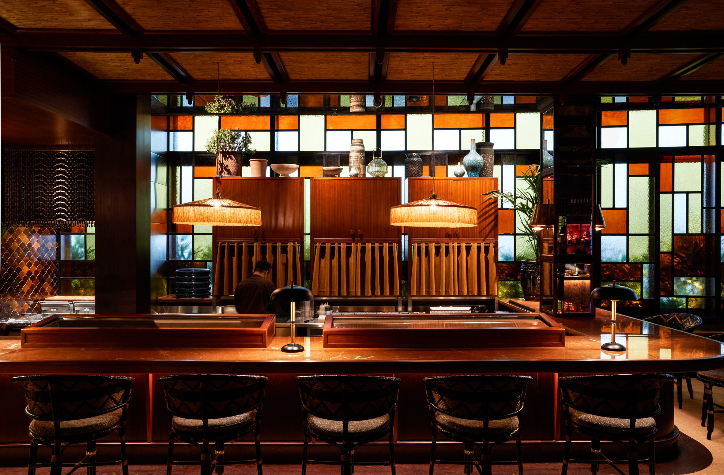 Sushi counter in front of stained glass windows in interior by Pirajean Lees