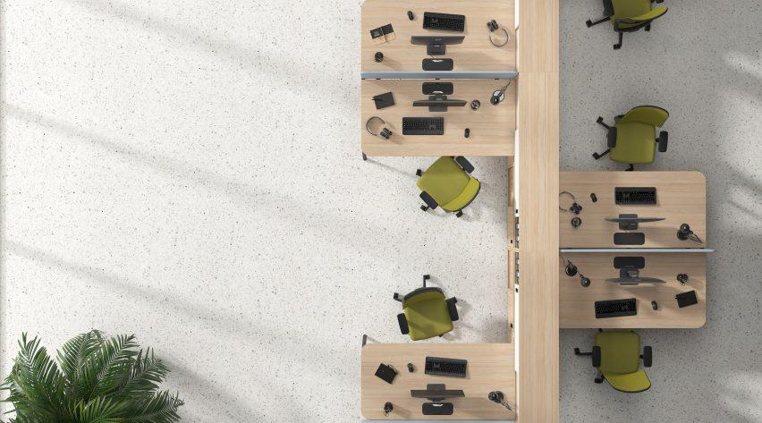 Pale wood desks configured into workstations around a dividing cabinet