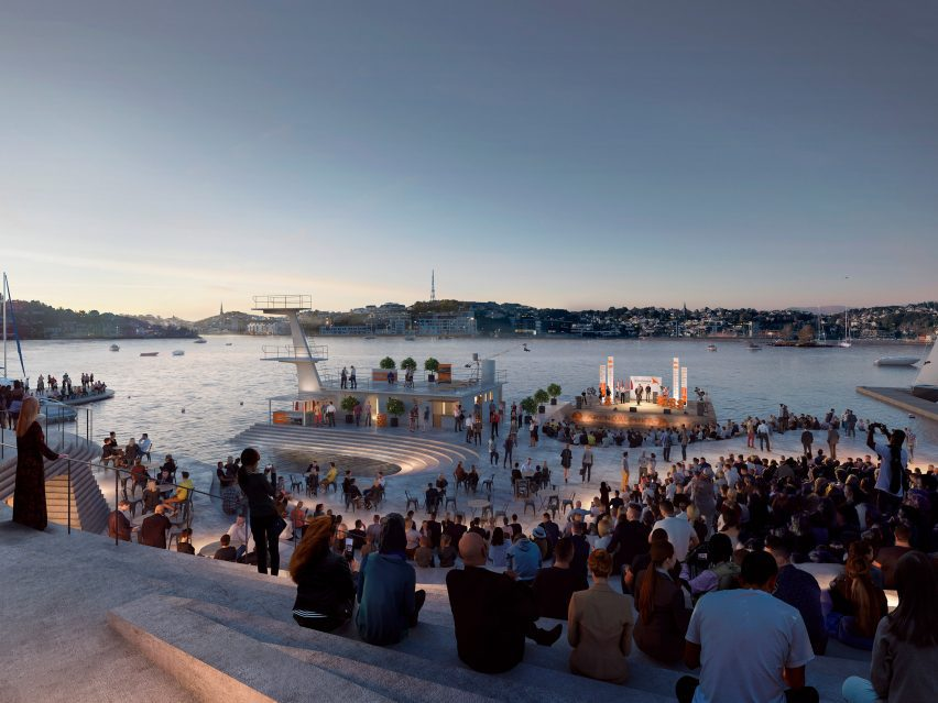 People sitting on amphitheatre seating watching an open-air performance on the harbour