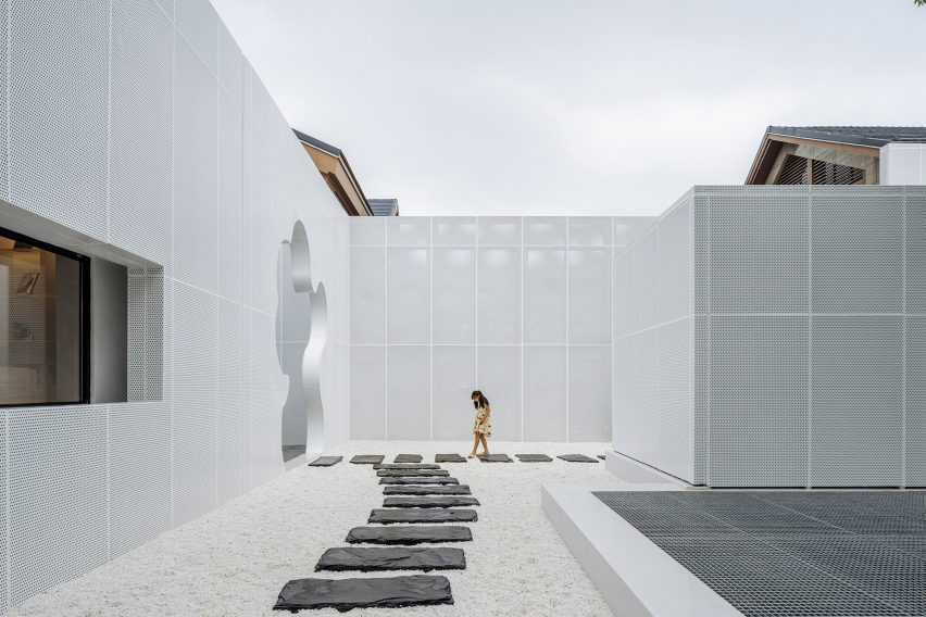 Courtyard with white pebbles surrounded by perforated white aluminium facade by Wutopia Lab