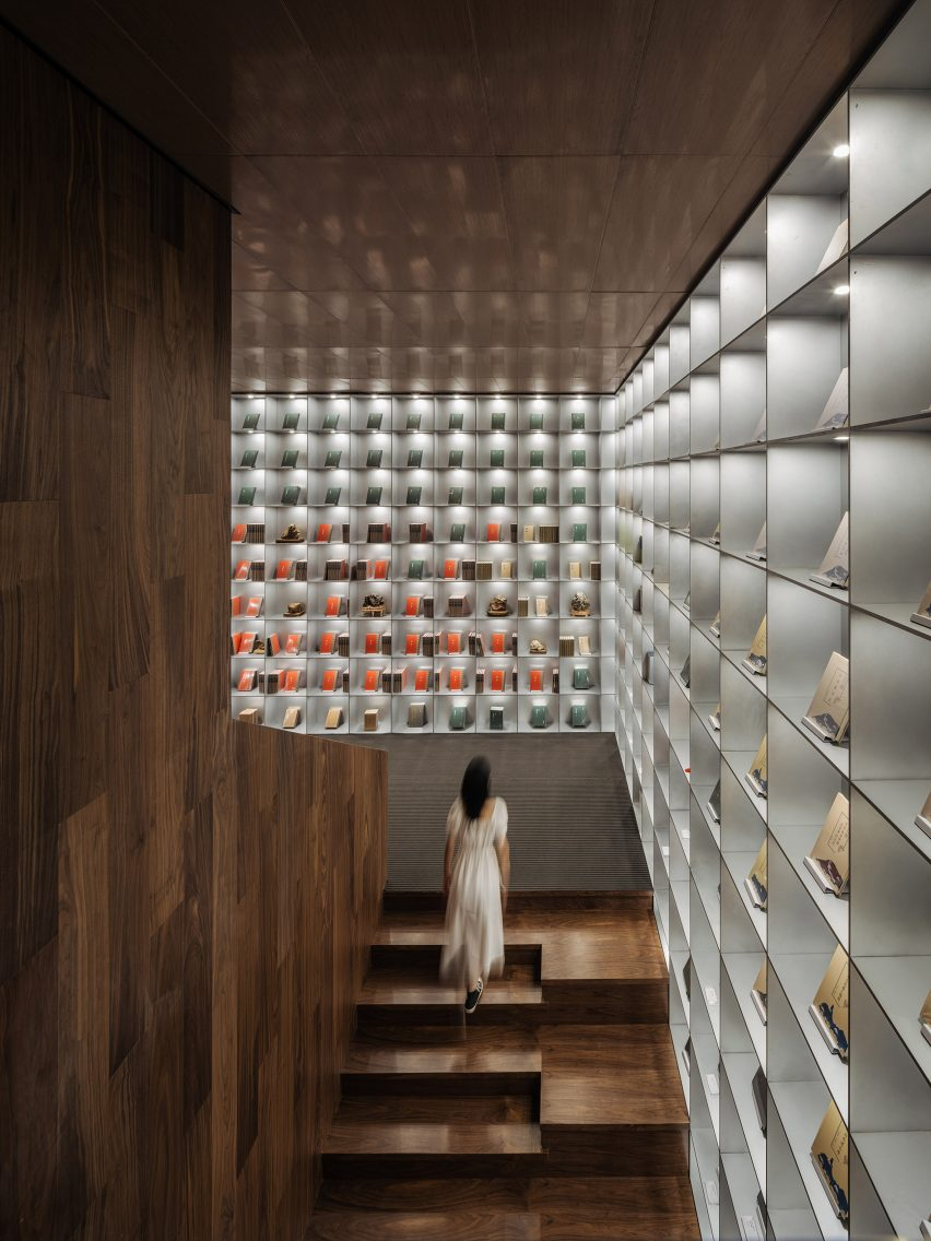 Wood-panelled staircase with book displays designed by Wutopia Lab