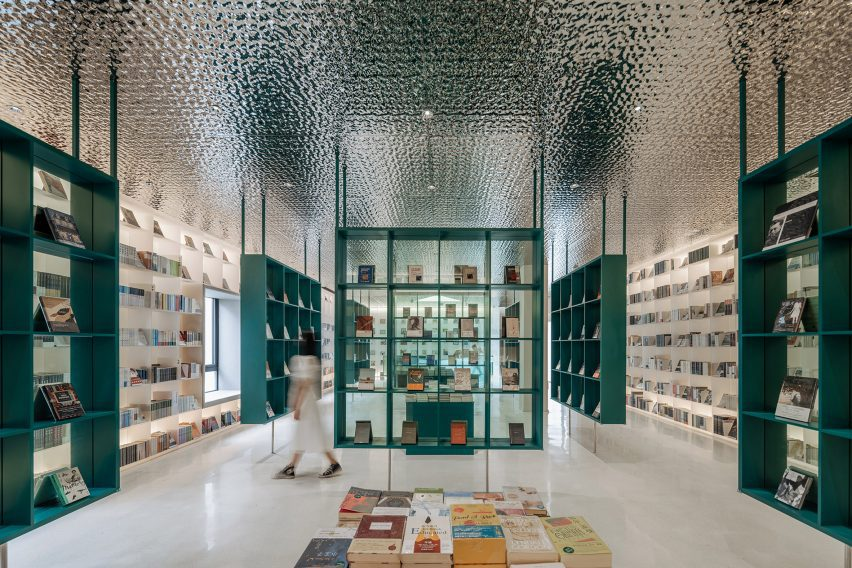 Bookshop by Wutopia Lab with petrol blue display stands and corrugated aluminium ceiling