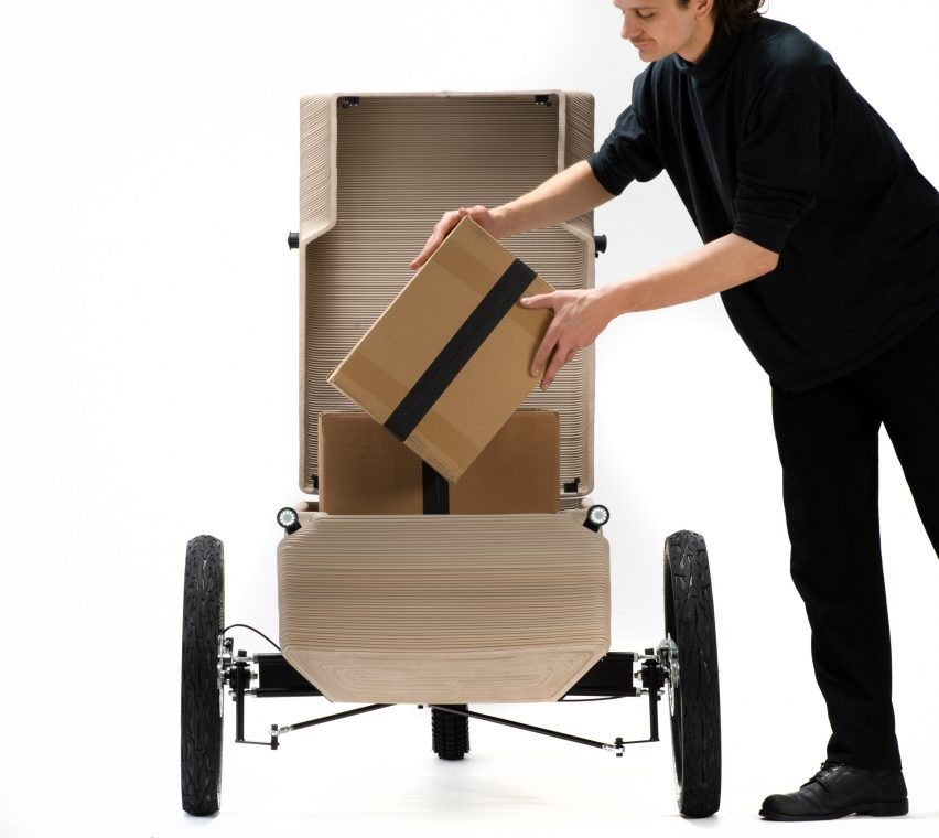 Man putting a box into the storage compartment of an electric tricycle by EOOS NEXT