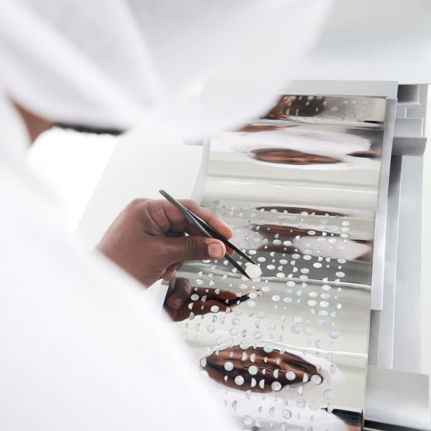 A photograph of a person placing pearls into a decorative piece