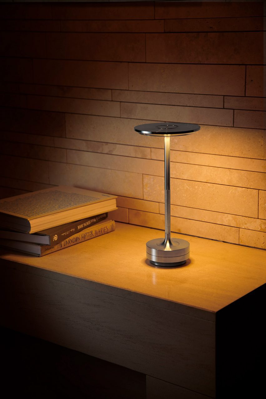 Turn portable lamp in aluminium on a desk with low lighting