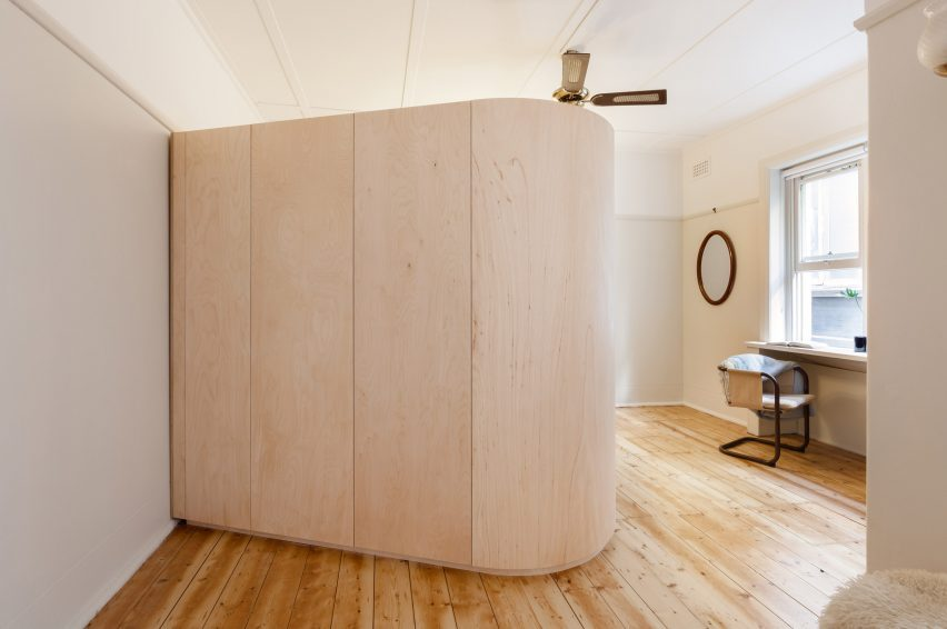 A plywood volume conceals a bed and storage