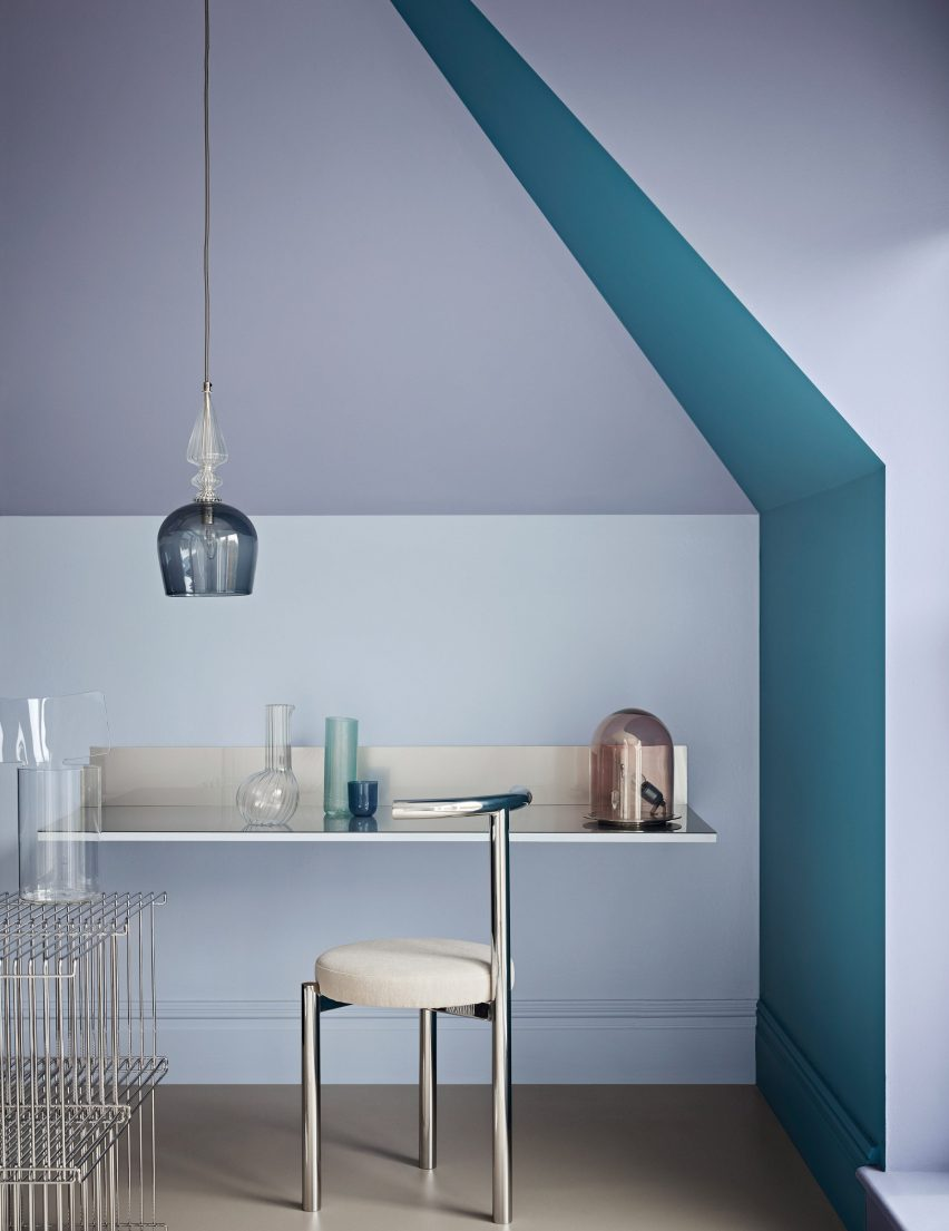 Desk nook with transparent, crystal-like objects and metal furniture against pale blue, grey and teal walls