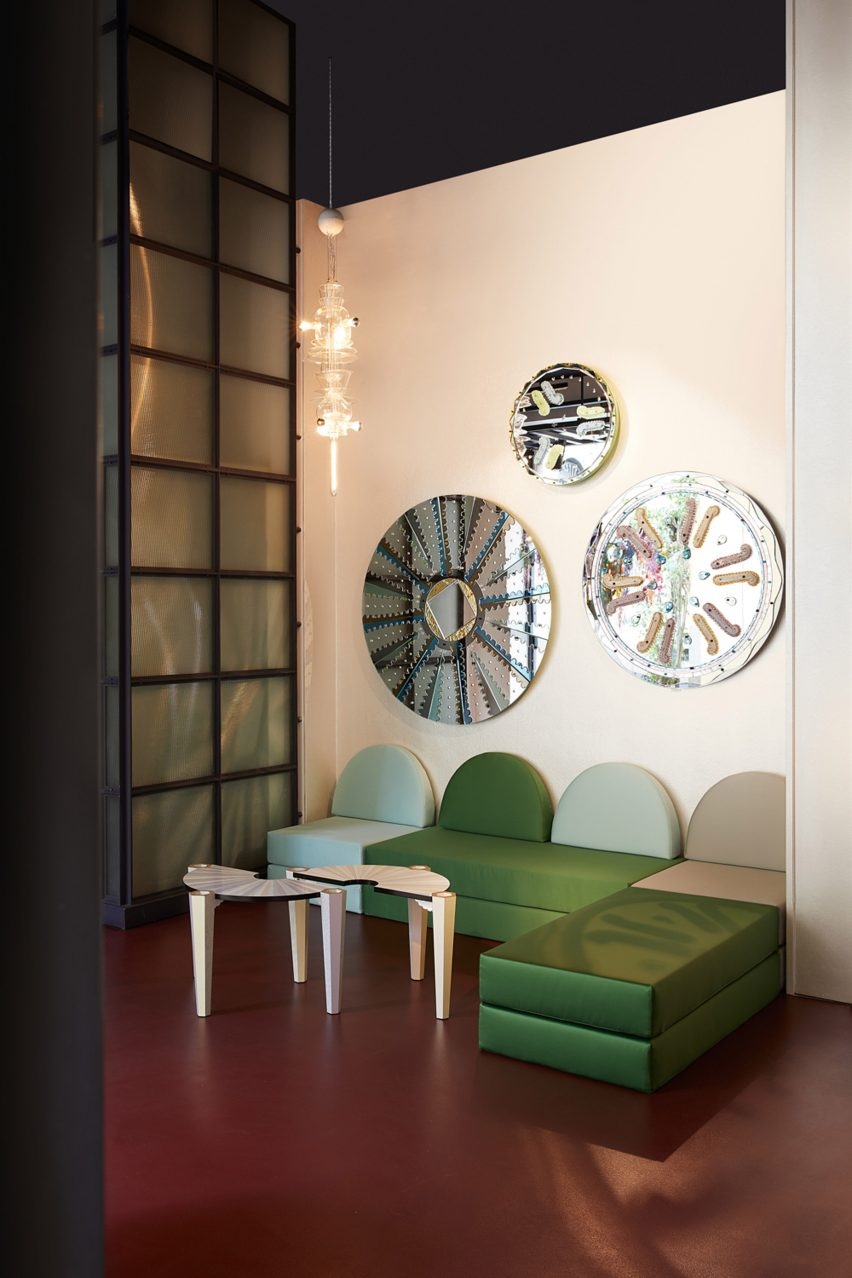 Green sofa under circular mirrors