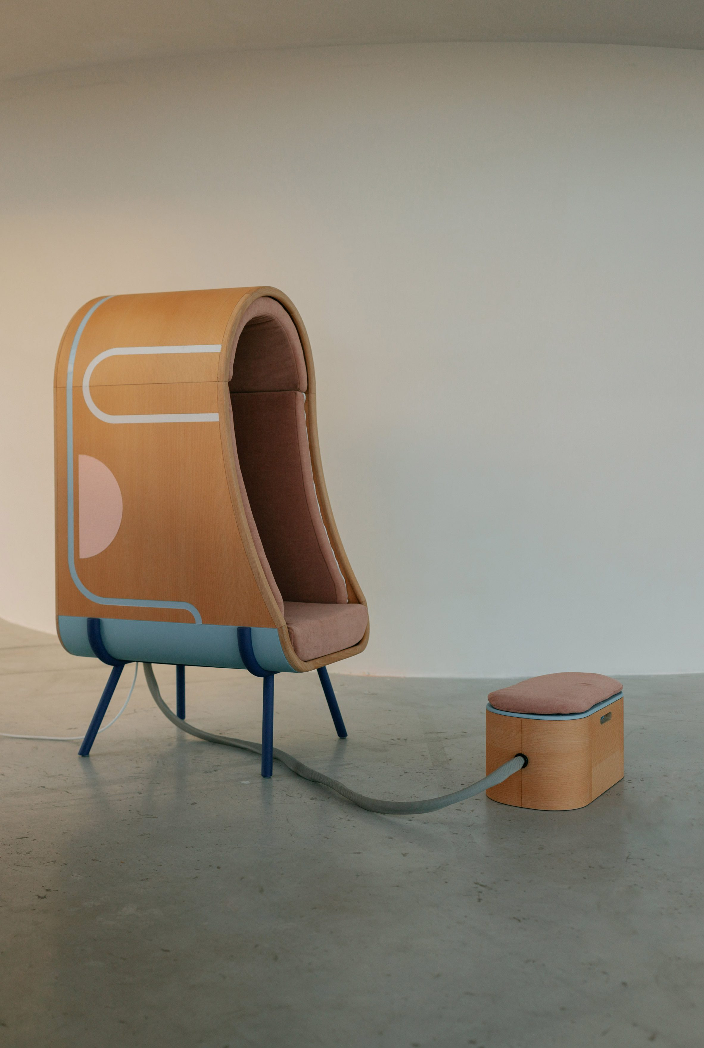 Wooden cocoon chair by Alexia Audrain with footrest