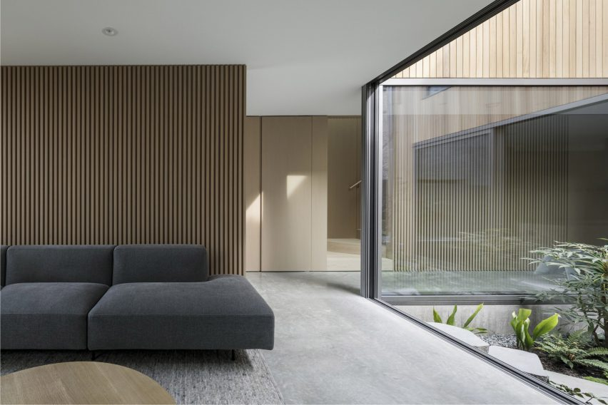 A living room with large window that looks onto a courtyard