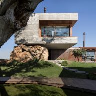 Fig House by Stemmer Rodrigues appears supported by a natural rock formation