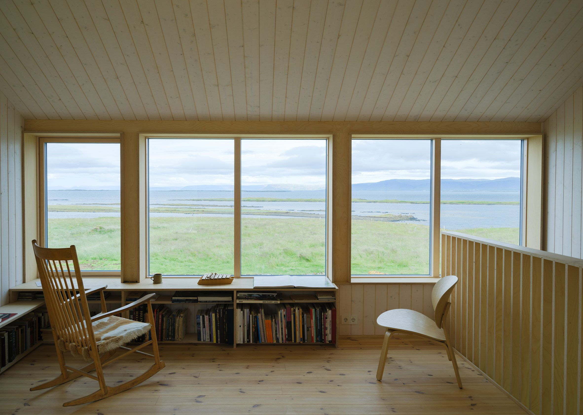 A wood-lined living room overlooking a nature reserve