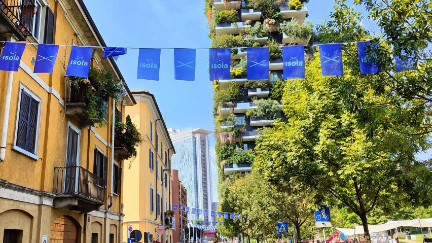 Blue flags hanging across a sunny street at Isola Design Festival