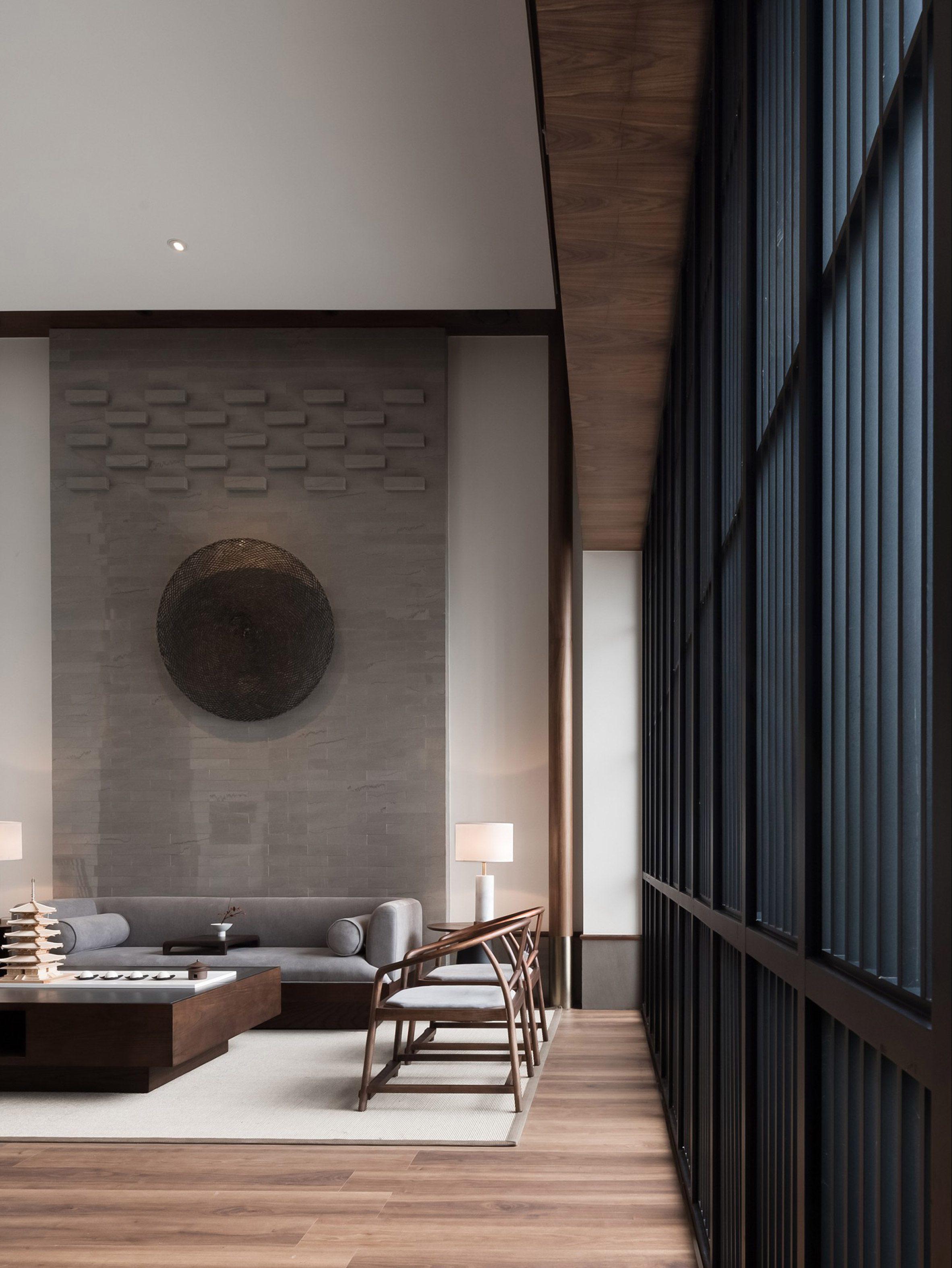 Гостиная с деревянными стульями и серым диваном от JG Phoenix