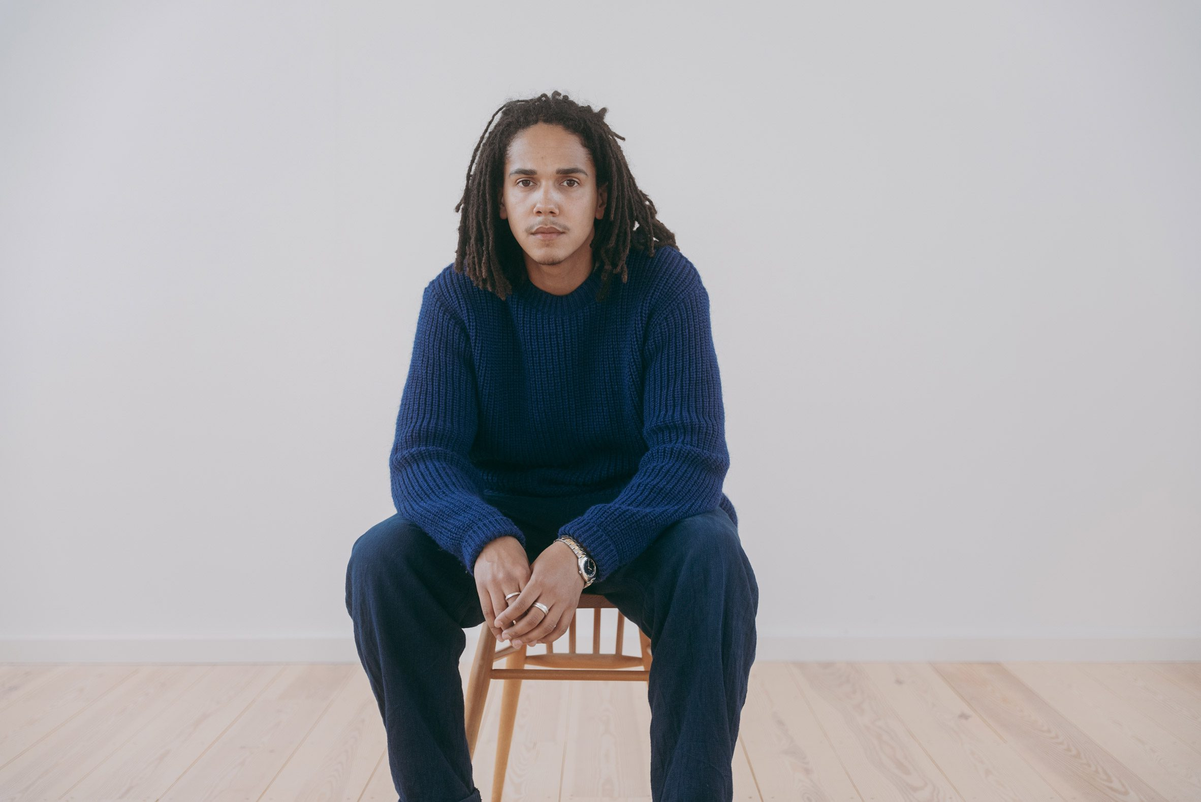 Mac Collins sitting on a wooden chair