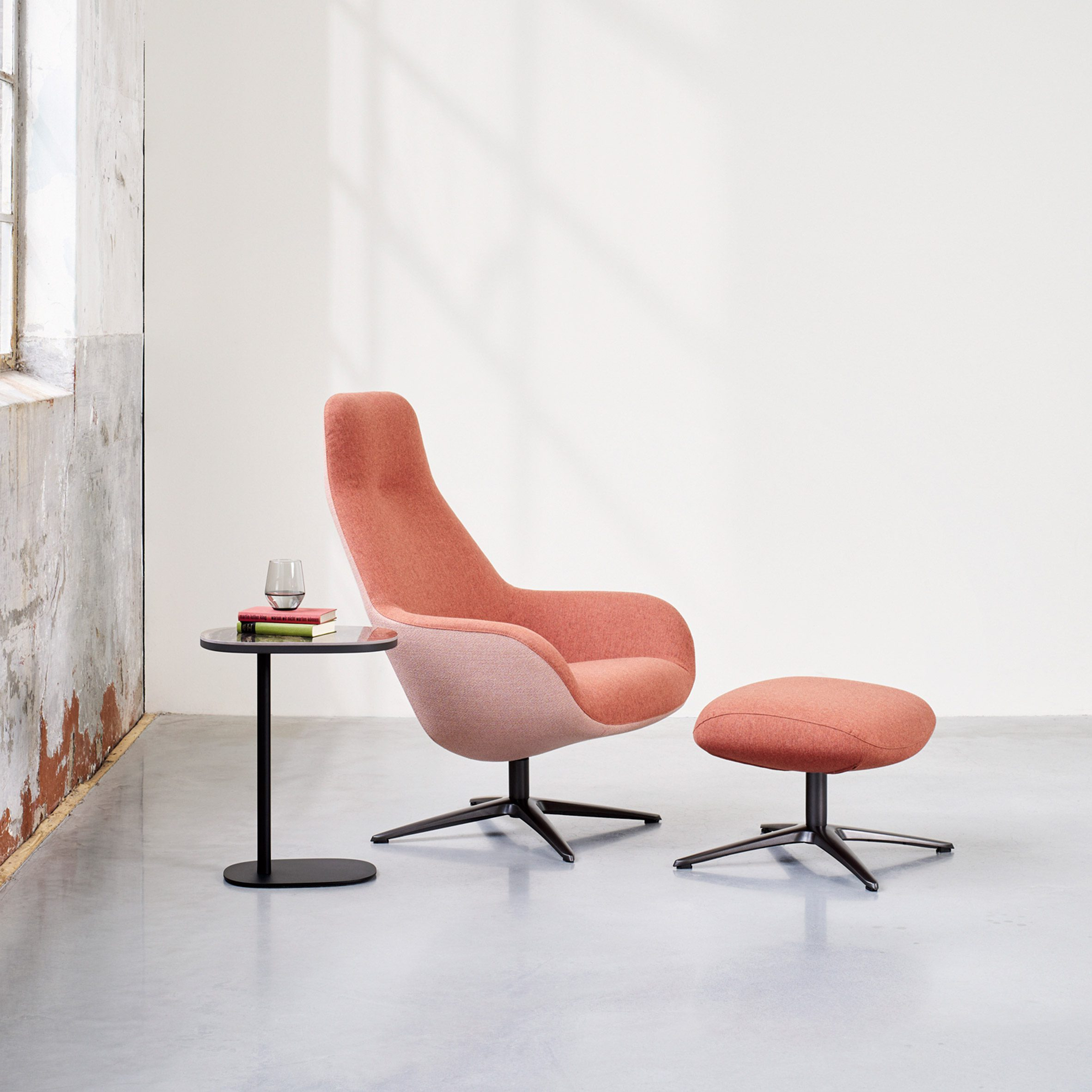 A pink high-backed LXR03 chair and footstool