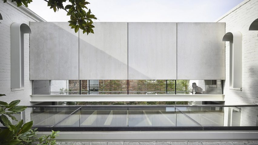 A glass bridge connects the volumes